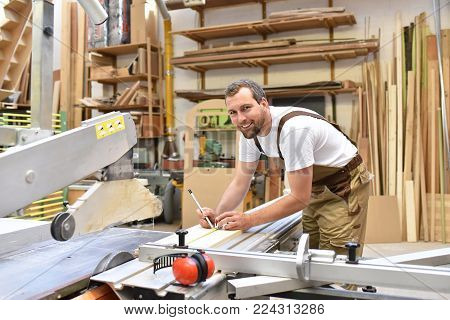 Friendly Carpenter With Ear Protectors And Working Clothes Working On A Saw In The Workshop