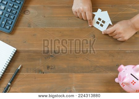 Top view of hands holding house paper with calculator, notebook and piggy bank