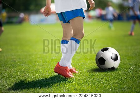Feet of football player with soccer ball. Soccer players before kick pass to teammate