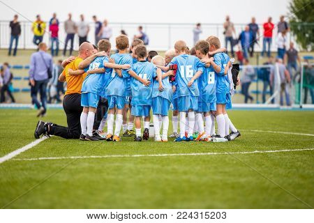 Children soccer football team with coach. Group of kids standing together on the pitch. Coach giving children's soccer team instructions. Group pep talk. Coaching youth soccer team before the game