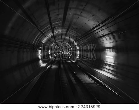 View of a subway tunnel from the front of a moving train. Fast underground train gaining speed in tunnel of the modern city. Underground train in Barcelona following its route.