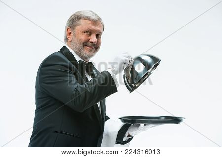 The senior waiter holding white towel and standing isolated on white studio background with tray and metal cloche lid cover. the concept of the best service and suggestions