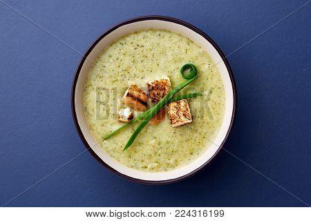 Vegan winter split pea turmeric soup on dark blue stone background. Top view, copy space.