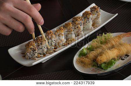 Hand hold chopstick on sushi restaurant table, eat sushi rolls
