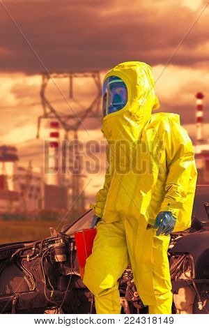 View of nuclear power plant and firefighter in a chemical protective hazmat suit next the demaged car.