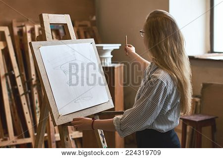 Tear view of a young student girl with beautiful hair drawing a Doric capital with a pencil on a wooden easel as her university assignment in a studio.