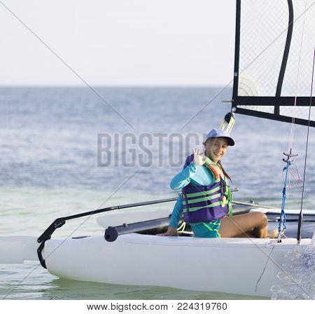 Beautiful Teenager Sailing Catamaran In Beautiful Sunset.