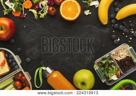 Healthy food background. Variety of fruits and vegetables, organic homemade snacks in lunch boxes and detox juice bottle on black background with copy space, top view