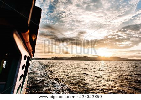 Sunrise near Flores. Boat trip to the islands of Komodo National Park in East Nusa Tenggara, Indonesia. Part of the wooden boat is visible in the photo