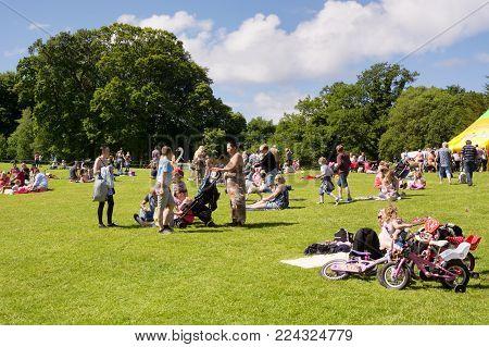 Calzean estate, Ayrshire, Scotland, UK: July 25, 2015 - Many people, families with children enjoying a warm sunny day on the lawns of the Calzean estate, Scotland