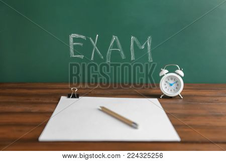 Table with alarm clock, sheets of paper and word EXAM written on chalkboard