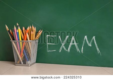 Holder with pencils and word EXAM written on chalkboard