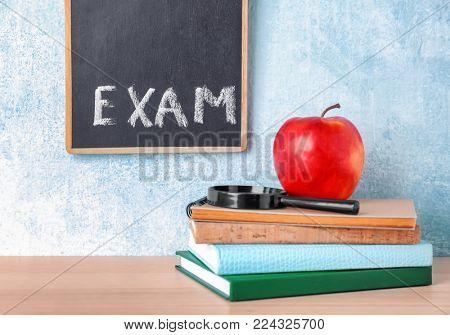 Blackboard with word EXAM, notebooks and apple on table