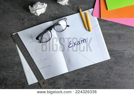 Notebook with word EXAM on table