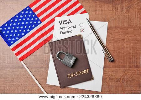 Passport with lock and USA flag on table. Denied American visa