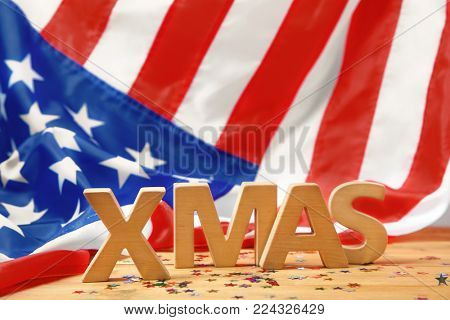 Word XMAS made of wooden letters on table against blurred American flag