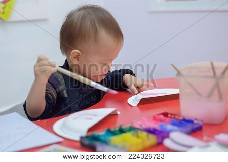 Asian toddler painting with paintbrush & watercolors in palette at art class, kid painting with nursery teacher ,Creative play for toddlers & do it yourself diy toys concept, Shallow depth of field