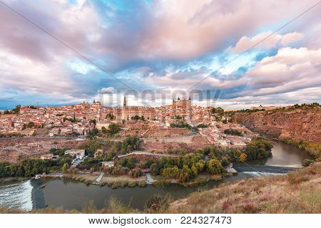 Panorama of Old city of Toledo with Cathedral, Alcazar and river Tajo at dusk, Castilla La Mancha, Spain