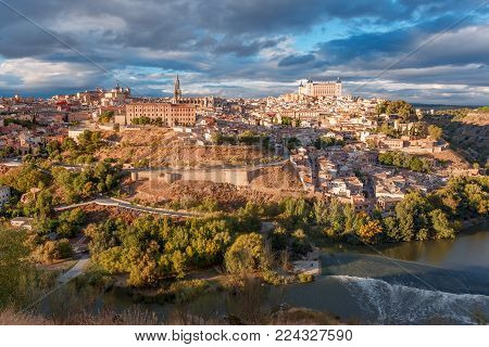 Panoramic aerial view of Old city of Toledo with Cathedral, Alcazar and river Tajo at dusk, Castilla La Mancha, Spain