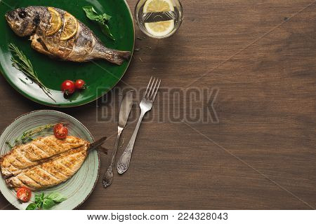 Restaurant food - whole grilled dorado and white fish on wooden restaurant table with cutlery, mediterranean cuisine, top view, copy space