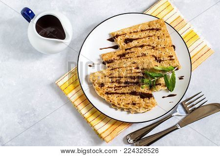 Thin russian pancakes with chocolate sauce. Prepare for holiday Maslenitsa in honor of end of winter. Pancakes on plate, chocolate sauce in gravy boat, mint and yellow napkin on light gray background