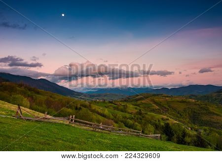 rural area at dusk with moon on cloudy sky. beautiful mountainous landscape with agricultural fields and wooden fences on grassy slopes in springtime
