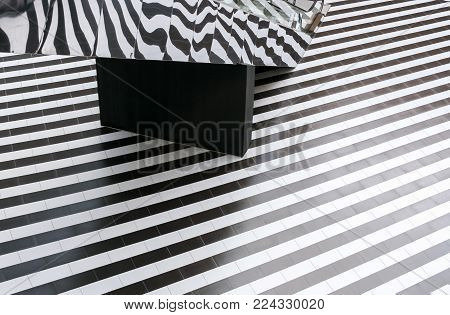 Abstraction. Geometric pattern of regular alternating black and white floor stripes and mirrored escalator, reflecting it.