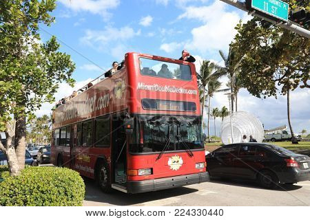 MIAMI BEACH, FLORIDA/USA - JANUARY 7, 2017:  Double decker bus tours are a popular way to see the city.  This one is cruising Ocean Drive.