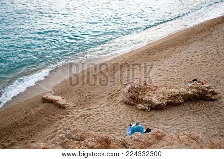 people having a rest on a deserted beach by the sea