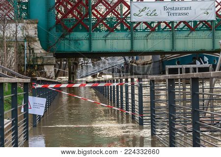 ISSY LES MOULINEAUX near PARIS, FRANCE - January 24, during the flood of winter, a billboard forbids access to the river where it is written - flooded area forbidden access to the public