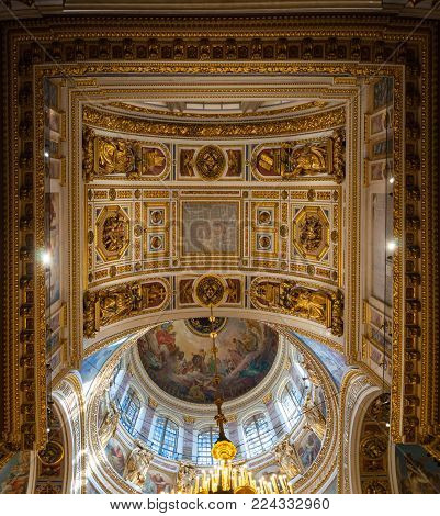ST PETERSBURG, RUSSIA - AUGUST 15, 2017. Ceiling ornated with sculptures and Bible paintings in the interior of the St Isaac Cathedral in St Petersburg, Russia. High angle view of St Petersburg Russia landmark