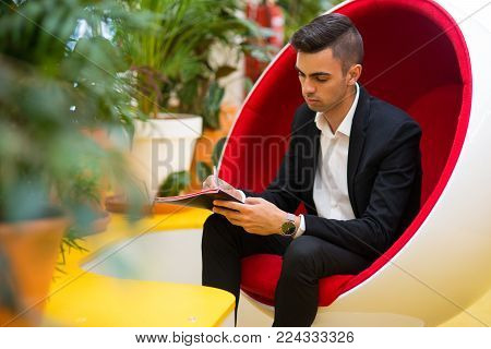 Concentrated young businessman making notes in document while sitting in comfortable armchair. Busy lawyer planning timetable or writing tasks on paper. Filling form concept