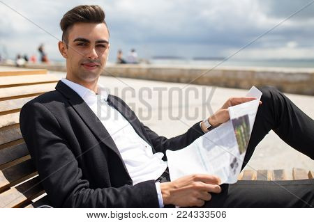 Confident young business analyst reading newspaper while holding expertise for stock market. Serious successful businessman enjoying morning newspaper outdoors. Publication concept