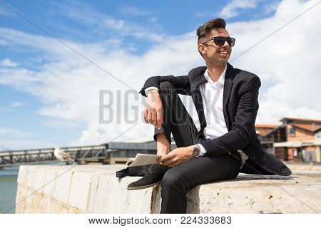 Happy handsome businessman relaxing on pier and looking around. Cheerful excited young man in formalwear feeling free and enjoying vacation. Young entrepreneur concept