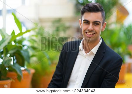 Optimistic young intern confident in himself looking at camera in winter garden. Happy confident businessman enjoying his success. Entrepreneur concept