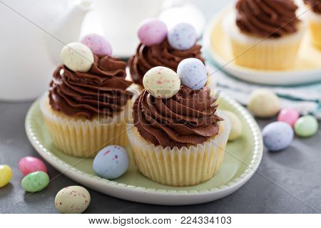 Easter vanilla cupcakes with chocolate frosting and candy eggs