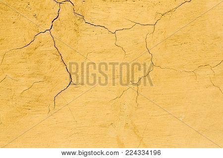 Rustic chapped painted wall texture abstract background. Shabby surface of yellow wall with cracks, textured backdrop with copy space