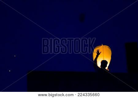 Silhouette of a man flying a paper sky lantern at dusk against a beautiful bluish night sky. These lanterns have become traditional during the festival of makar sankranti or uttarayan especially in Rajasthan india