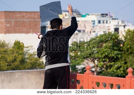 Man flying a kite from a rooftop on the indian festival of makar sankranti or uttaryan in Rajasthan or gujrat. These fighting kites are a traditional competition
