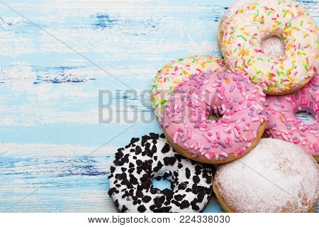 Traditional donuts on white wooden background.  Tasty doughnuts with icing and powdered sugar, copy space
