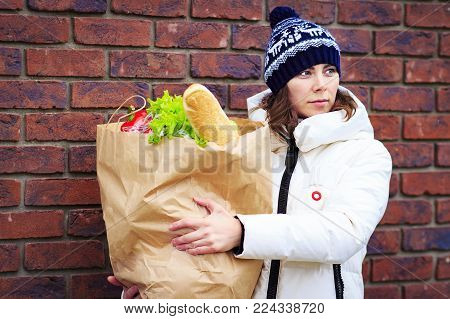 girl shopping at grocery store. Attractive woman with paper food product package. woman holding grocery shopping bag with vegetables.