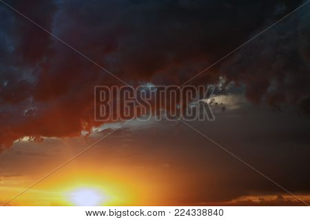 summer landscape, sunset with golden rays of the sun against a dark sky with dark thunderclouds