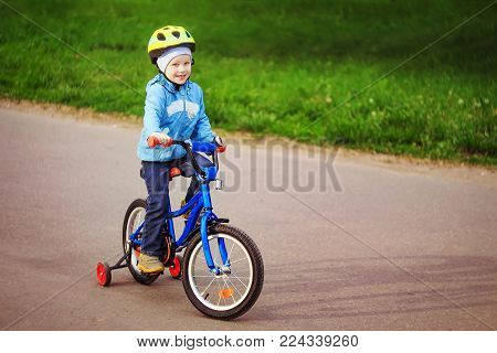 boy rides bike along the city path in the park. small bicyclist in helmet riding bicycle