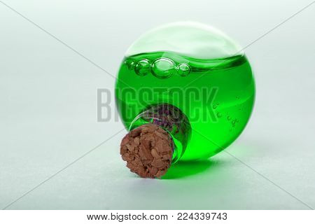 green liquid in old style vial. close up