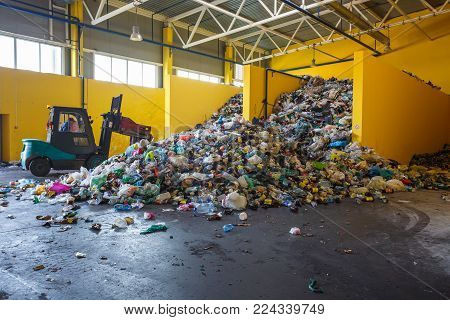 GRODNO, BELARUS - OCTOBER 16, 2017: Plastic at the modern waste hazardous processing plant. Recycling and storage of waste for further disposal. Truck sorts and separate garbage plastic bottles