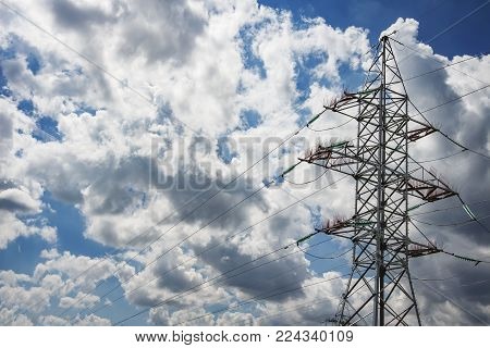 High-voltage power line against the background of clouds and blue sky. Electricity and power engineering concept. Transmission of electrical power by wire