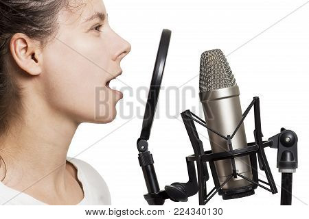Brunette girl records voice to studio microphone. Young woman sings in studio condenser microphone with spider isolated on white background. Write song in sound recording studio