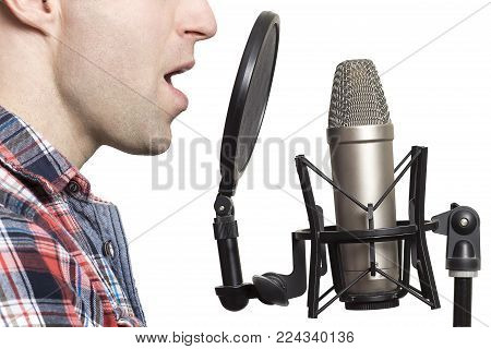 Record voice to microphone in studio. young man sings in studio condenser microphone with spider isolated on white background. Write song in sound recording studio
