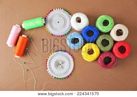 Sewing threads and crocheting clews with pins on color background, top view