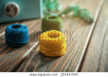 Color crocheting clews on wooden table